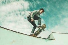 Faceta deskorolkarz jedzie deskorolka na skatepark Młodego człowieka doskakiwanie z deskorolka fotografia royalty free