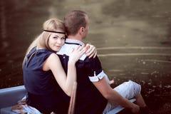Faceta i dziewczyny obsiadanie na krawędzi łodzi zdjęcia stock