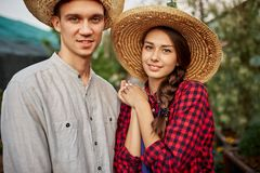 Faceta i dziewczyny ogrodniczki w słomiani kapelusze stoją wpólnie w ogródzie na słonecznym dniu obraz stock
