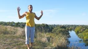 Faceta joga ćwiczy pozycje i ruchy outdoors Młody człowiek pozycja przy joga pozą przy naturą Atleta robi sile Zdjęcia Stock