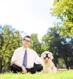 Faceta obsiadanie na trawie obok jego Labrador retriever psa w p Obraz Stock