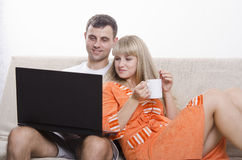 Faceta obsiadanie z jego laptopem na leżance, siedzi obok dziewczyny z filiżanką herbata Obrazy Royalty Free