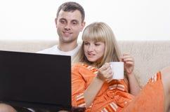 Faceta obsiadanie z jego laptopem na leżance, siedzi obok dziewczyny z filiżanką herbata Obrazy Stock