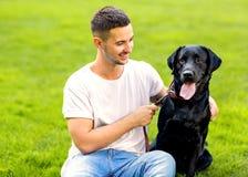 Faceta przytulenie z jego psim labradorem bawić się w parku obrazy royalty free