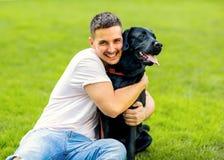 Faceta przytulenie z jego psim labradorem bawić się w parku fotografia royalty free