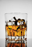 Faceted amber glass with whiskey and ice Stock Photography