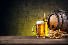 Faceted glass of beer, bottle and barrel. On yellow background stock photos