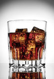 Faceted glass of cola with ice Royalty Free Stock Photography