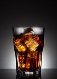 Faceted glass of cola with ice Stock Images