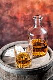Faceted glass and dusty decanter of brandy and Stock Photo