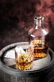 Faceted glass and dusty decanter of brandy Stock Photos
