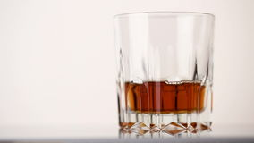 Faceted glass filled with whiskey and ice cubes stock footage