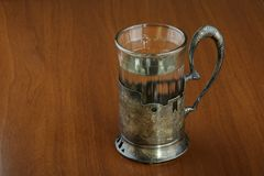 Faceted glass of hot water for tea in an ancient silver cup holder Royalty Free Stock Photo