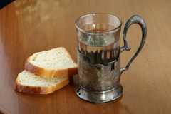 Faceted glass of hot water for tea in an ancient silver cup holder and two slices of bread Royalty Free Stock Image