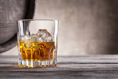 Faceted glass of whiskey and the angle of wooden barrels Royalty Free Stock Photos
