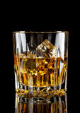 Faceted glass of whiskey with ice Royalty Free Stock Images
