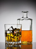 Faceted glass of whiskey with ice and a bottle Royalty Free Stock Photos