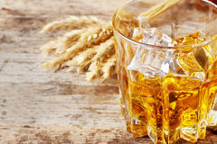 Faceted glass of whiskey with ice and ears Stock Image
