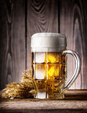 Faceted mug of light beer with foam and ears Royalty Free Stock Image