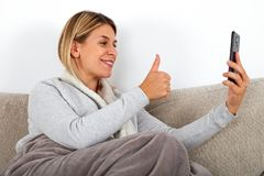 Facetime - thumbs up. Attractive young woman talking with friend on facetime, showing thumbs up while relaxing on the sofa stock photo