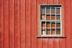 Fachada abandonada de la casa con la pared de madera roja de la vieja peladura y la ventana de cristal rota grunge Imagenes de archivo