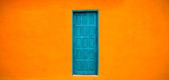 Fachada alaranjada brilhante vívida da cor com a porta fechado azul esverdeado no centro do grande fundo largo alaranjado vazio d Imagem de Stock Royalty Free