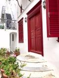 Fachada blanca colorida de la casa con las puertas, la escalera y los obturadores rojos en la isla de Mykonos foto de archivo libre de regalías