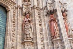 Fachada com esculturas do século XVI de Roman Catholic Seville Cathedral, Espanha Padre e Bíblia da leitura das mulheres imagem de stock royalty free