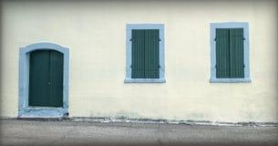 Fachada con la puerta vieja y pequeñas ventanas imagenes de archivo