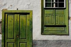 Fachada con la ventana verde una puerta Fotos de archivo