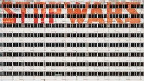 Fachada constructiva abandonada con lema de la pintada - pare las guerras foto de archivo libre de regalías