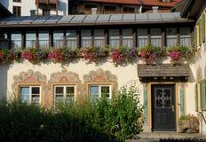 Fachada da casa com três janelas e uma porta muitos potenciômetros de flor em Oberammergau em Alemanha Fotografia de Stock
