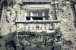 Fachada da casa destruída velha com janelas quebradas Fotos de Stock