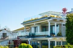 A fachada da casa residencial luxuosa enfrentou a uma margem da baía imagem de stock