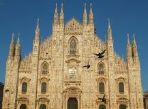 Fachada da catedral do domo em Milão contra o céu azul, iluminada pelo sol de ajuste dourado imagens de stock royalty free