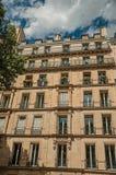 Fachada da construção com balcão e da árvore frondosa em Paris foto de stock