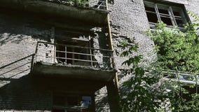 A fachada da construção de tijolo destruída velha com janelas quebradas dentro no bloco de cidade do gueto A demolição do velho video estoque