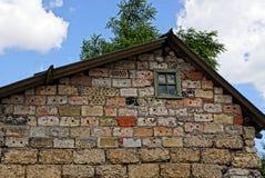 A fachada da construção de tijolo velha com uma janela pequena Imagens de Stock