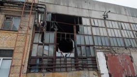 Fachada da construção industrial velha para a demolição no dia nebuloso, em quadros de vidro e destruídos quebrados video estoque