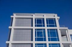 Fachada da construção moderna do negócio com as grandes janelas espelhadas e do balcão contra o céu azul imagens de stock royalty free