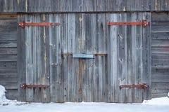 Fachada da garagem com portas de madeira cinzentas velhas Porta velha da garagem fotos de stock