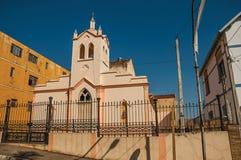 Fachada da igreja e da torre de sino pequenas atrás da cerca do ferro, em um dia ensolarado em São Manuel fotografia de stock royalty free