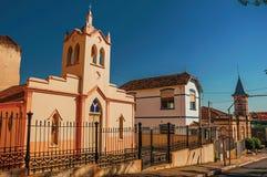Fachada da igreja e da torre de sino pequenas atrás da cerca do ferro, em um dia ensolarado em São Manuel fotos de stock royalty free