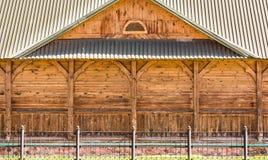 A fachada da parte de uma construção de madeira velha com colunas decorativas e um telhado feito do perfil do metal, parede sem j Imagem de Stock