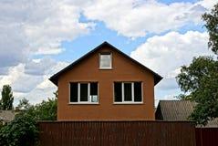 Fachada de Brown de uma construção privada com janelas atrás de uma cerca de madeira Fotos de Stock Royalty Free