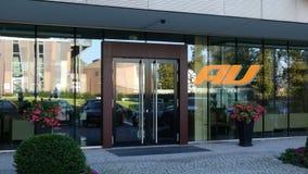 Fachada de cristal de un edificio de oficinas moderno con el logotipo móvil de la compañía telefónica del au Representación edito Fotografía de archivo