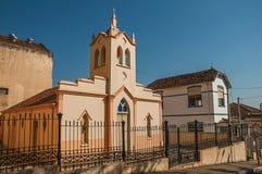 Fachada de la pequeños iglesia y campanario detrás de la cerca del hierro, en un día soleado en São Manuel Foto de archivo libre de regalías