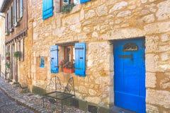 Fachada de las casas de piedra con las puertas de madera y las ventanas azules fotos de archivo