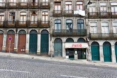 Fachada de las historias más inferiores de un edificio de apartamentos en una calle escarpado inclinada del guijarro en Oporto, Po Fotos de archivo
