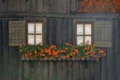 Fachada de madeira rural com janelas e flores na cidade Rhemes Notre Dame dos cumes Imagem de Stock Royalty Free